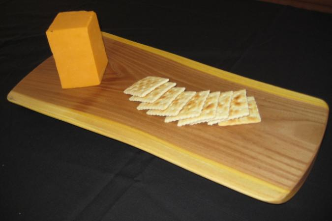 "The cheese board in reclaimed elm (7"" x 16"" x 1""). These boards in elm, or black walnut are the perfect size for setting out snacks for your guests. With their elegant, organic shapes , beautiful grain and color, this is a great way to present these reclaimed trees to your friends and family."